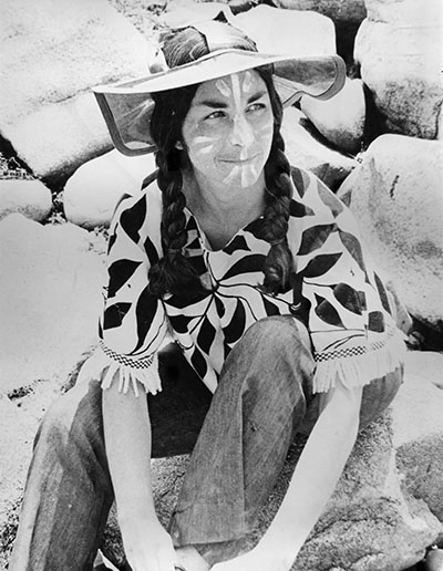 photo of roz payne sitting on rocks with face pain